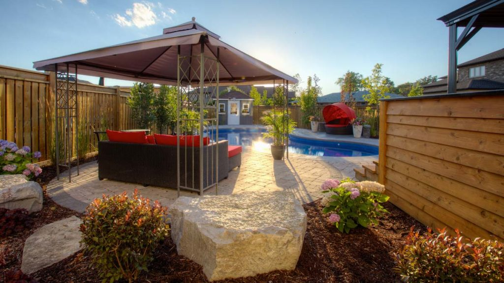 view of a back garden with stone patio and pool
